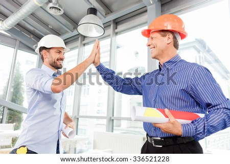 Well done work. Experienced two engineers are giving high five. They are standing and laughing. The men in helmets are holding blueprint of construction - stock photo