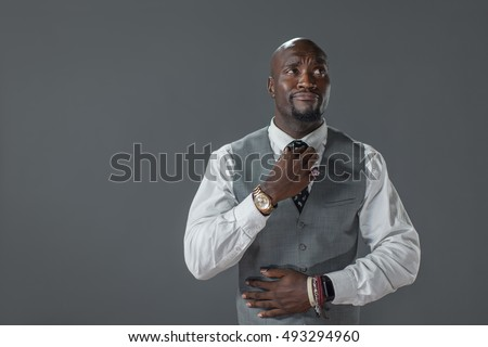 Well dressed African American man fixing his tie. Copy space on grey background.