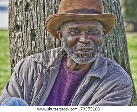 Well dressed afro-american homeless man with hat - stock photo