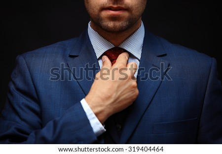 Well dressed business man adjusting his neck tie