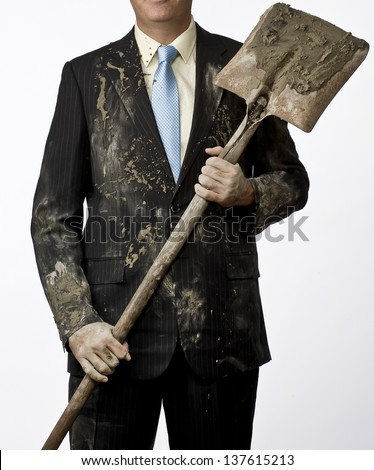 Well dressed business man holding a shovel with dirty clothes. Relationship between blue collar and white collar workers