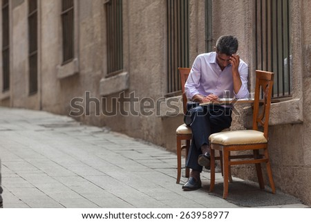 Well dressed business man smoking sitting on a small table on the street, istanbul, Turkey - 15/06/2014