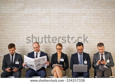 Well-dressed business people waiting for their turn to interview - stock photo