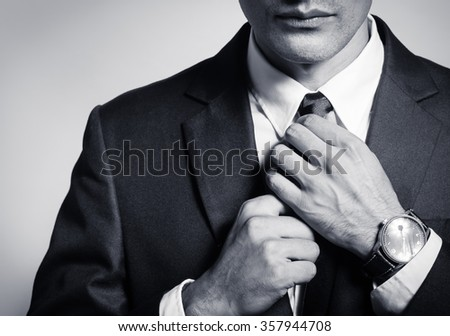 Well dressed businessman fixing his tie.  - stock photo