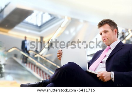 Well dressed businessman sitting in the lobby and using laptop computer. - stock photo