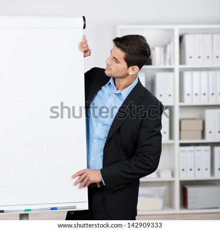 Well dressed businessman wearing a nice black suit looking at flipchart in the office.