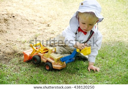 Well-dressed child(wedding participant) is playing with excavator on the grass. Boy is wearing white t-shirt, cap and bow-tie.