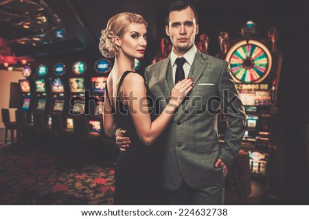 Well-dressed couple against slot machines - stock photo