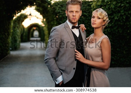 Well-dressed couple in a beautiful alley  - stock photo