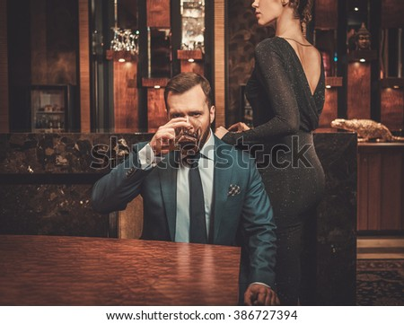Well-dressed couple in luxury apartment interior.