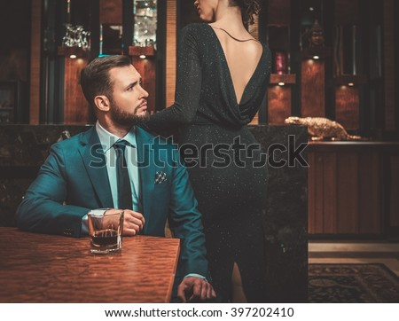 Well-dressed couple in luxury apartment interior. - stock photo