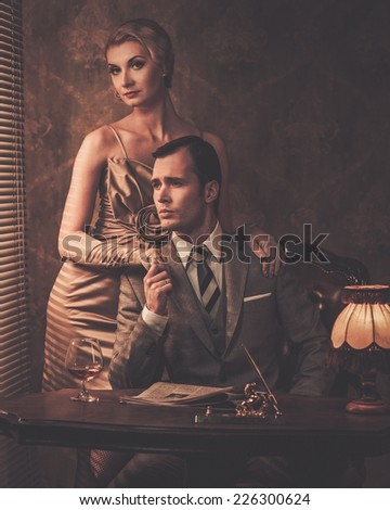 Well-dressed couple sitting behind table - stock photo