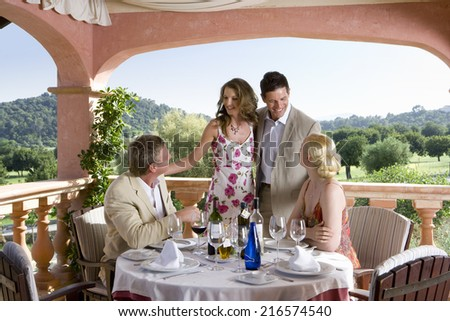 Well-dressed couples drinking wine at table on restaurant balcony - stock photo