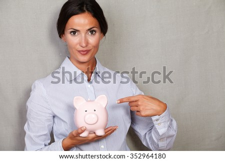 Well-dressed female pointing to piggy bank in formalwear and looking at camera on grey texture background