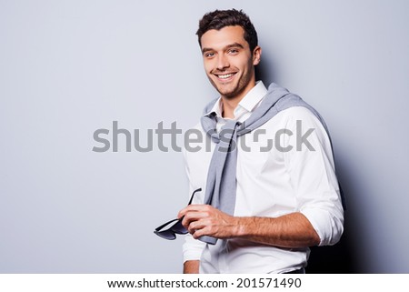 Well-dressed handsome. Handsome young man in smart casual wear holding his sunglasses and smiling while standing against grey background - stock photo
