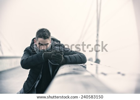 Well dressed handsome young detective or policeman or mobster standing in an urban environment aiming a firearm, hiding behind small wall with a determined expression, side view - stock photo
