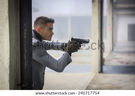 Well dressed handsome young detective or policeman or mobster standing in an urban environment holding a gun with a determined expression, coming from behind a column - stock photo