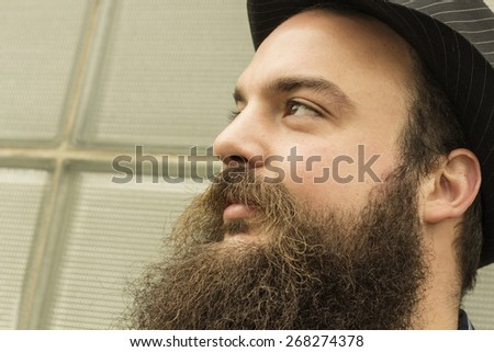 Well dressed happy bearded man sits against a glass building