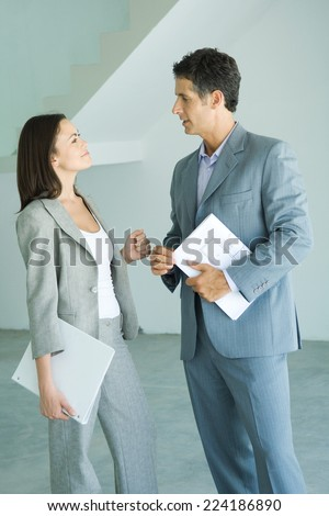 Well dressed man and woman standing in bare home interior, speaking, woman holding binder, man holding blueprints - stock photo