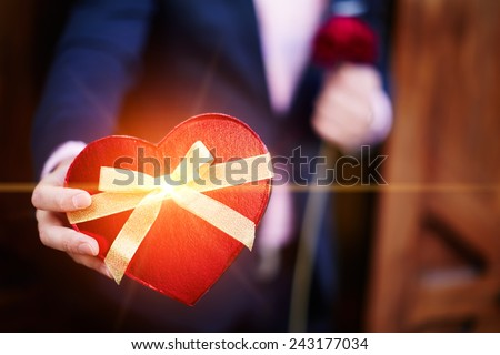 Well-dressed man giving a wonderful heart shape gift for lover on Saint Valentine's Day - stock photo