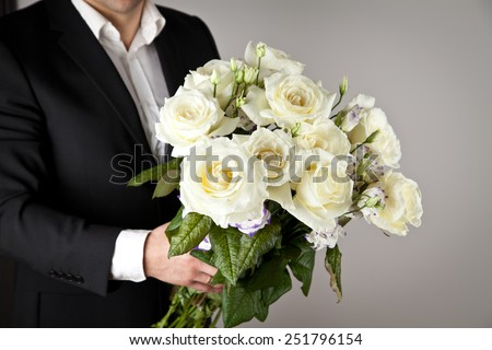 well-dressed man holding a bouquet of flowers, white roses. Holidays and celebrations. Wedding day. - stock photo