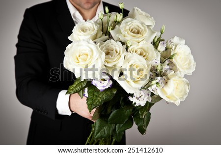 Well-dressed man holding a bouquet of white roses. Holidays and celebrations. Wedding day. - stock photo