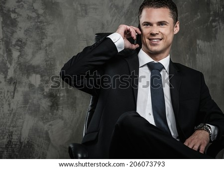 Well-dressed man in black suit with mobile phone