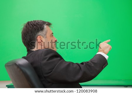 Well-dressed man sitting on office chair pointing to copyspace