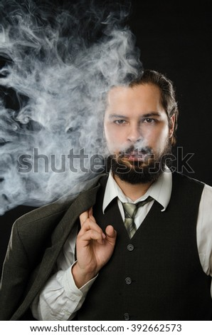 well-dressed man smoking electronic cigarette on black background