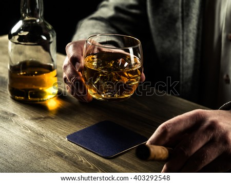 Well-dressed man with a cigar drinking whiskey