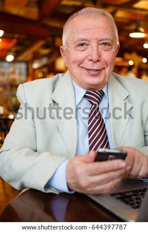 Well-dressed old senior businessman on smartphone connected to wireless internet sharing photo in social networks
