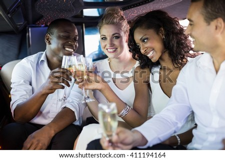 Well dressed people drinking champagne in a limousine on a night out - stock photo