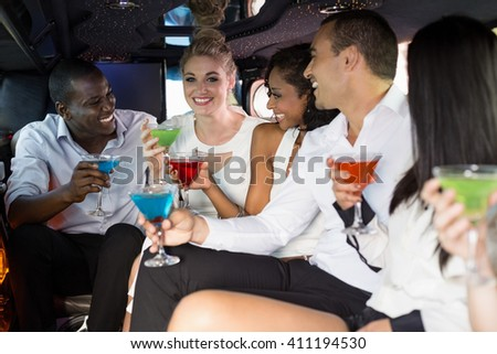 Well dressed people drinking cocktails in a limousine on a night out - stock photo