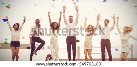 Well dressed people jumping next to limousine against flying colours