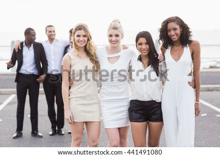 Well dressed people posing on a night out - stock photo