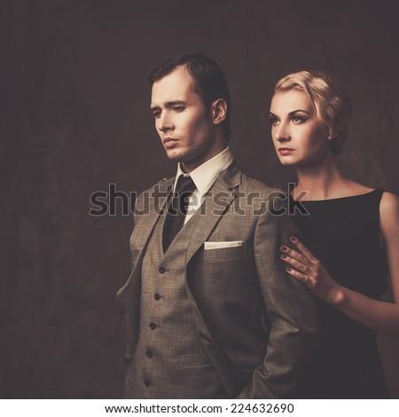 Well-dressed retro couple on grey background - stock photo