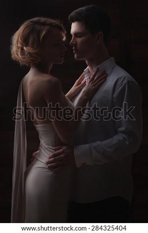Well-dressed retro couple over dark background - stock photo