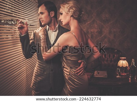 Well-dressed retro style couple near window - stock photo