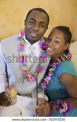 Well-dressed teenage couple with drinks outside school dance - stock photo