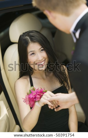 Well-dressed teenager girl being helped out of limo by date - stock photo