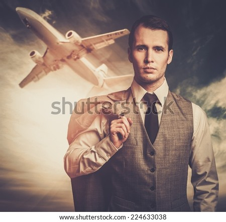Well-dressed traveling businessman against plane in the sky - stock photo
