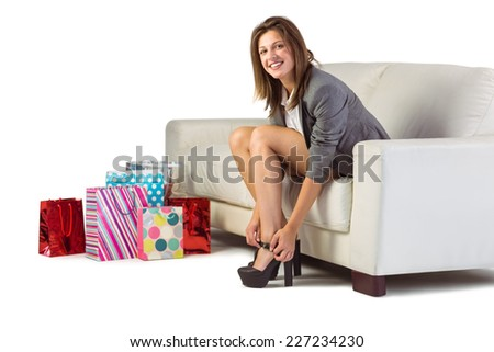 Well dressed woman sitting on couch taking off her shoes at home in the living room - stock photo
