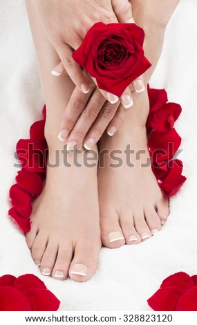 Well groomed female feet and hands with red roses. Pedicure. Manicure.