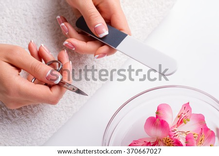 Well-groomed female hands on a towel. Women's hands with manicure tools.