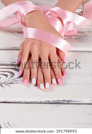 Well-groomed female hands with gentle pink ribbon. Nice white-pink spring manicure.
