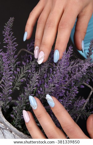 Well-groomed nail art design. pink blue and white colors of nail art. Nail polish. Beauty hands. Fashion Stylish Fashion Colorful Nails. Female hands leaning on the corset.