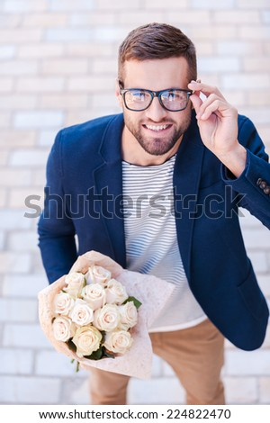 Well hello! Top view of cheerful young man in smart casual wear holding bouquet of flowers and adjusting his eyeglasses while standing outdoors  - stock photo