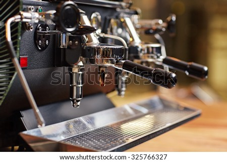 Well-kept espresso machine up close with the chrome looking shiny and the whole piece of equipment looking very clean