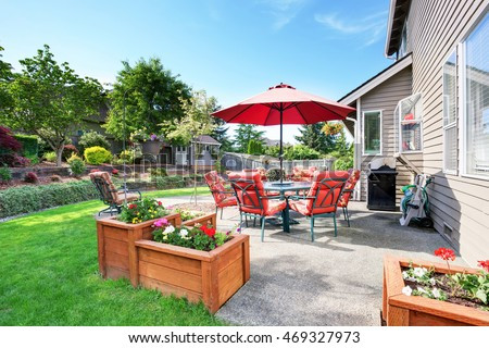 Well Kept Garden At Backyard With Concrete Floor Patio Area And Opened Red  Umbrella. Northwest
