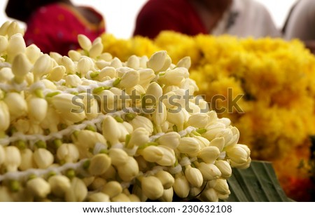 Well knitted jasmine flower with the seller in the background for sale in a traditional flower market in Chennai,Tamil Nadu,India - stock photo